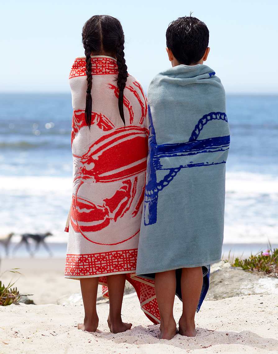 Kids wrapped in towels on the beach