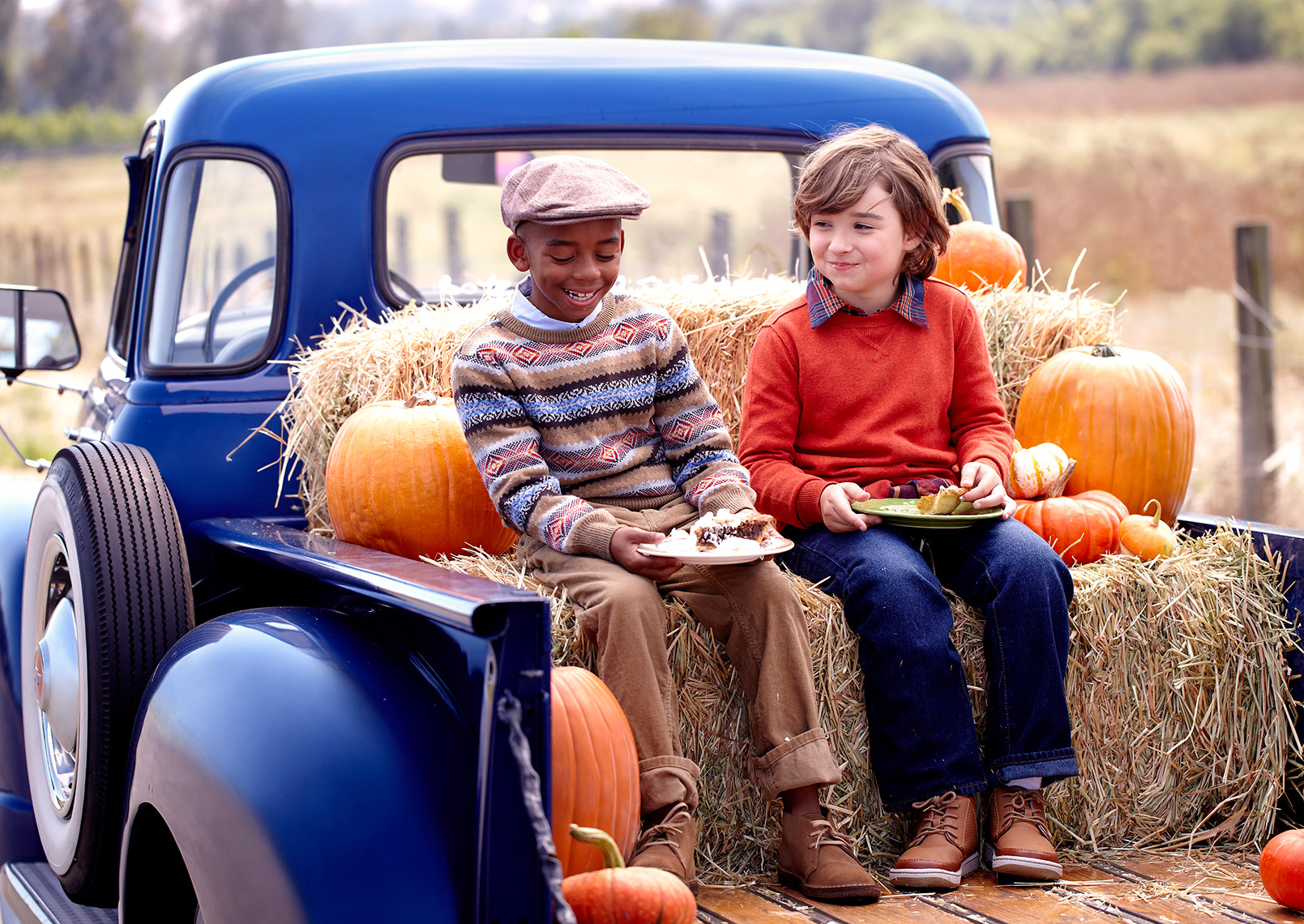 Two kids on a pickup truck eating pie