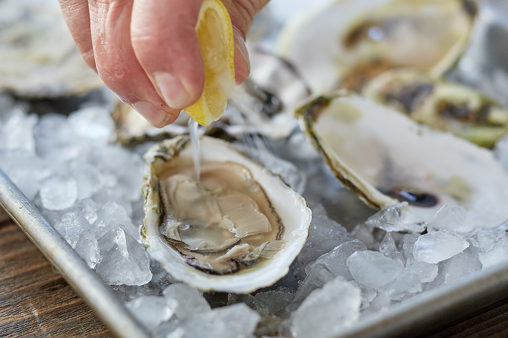 Squeezing lemon on a plate of oysters