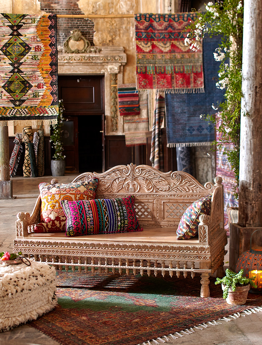 Hanging rugs and ornate bench at market