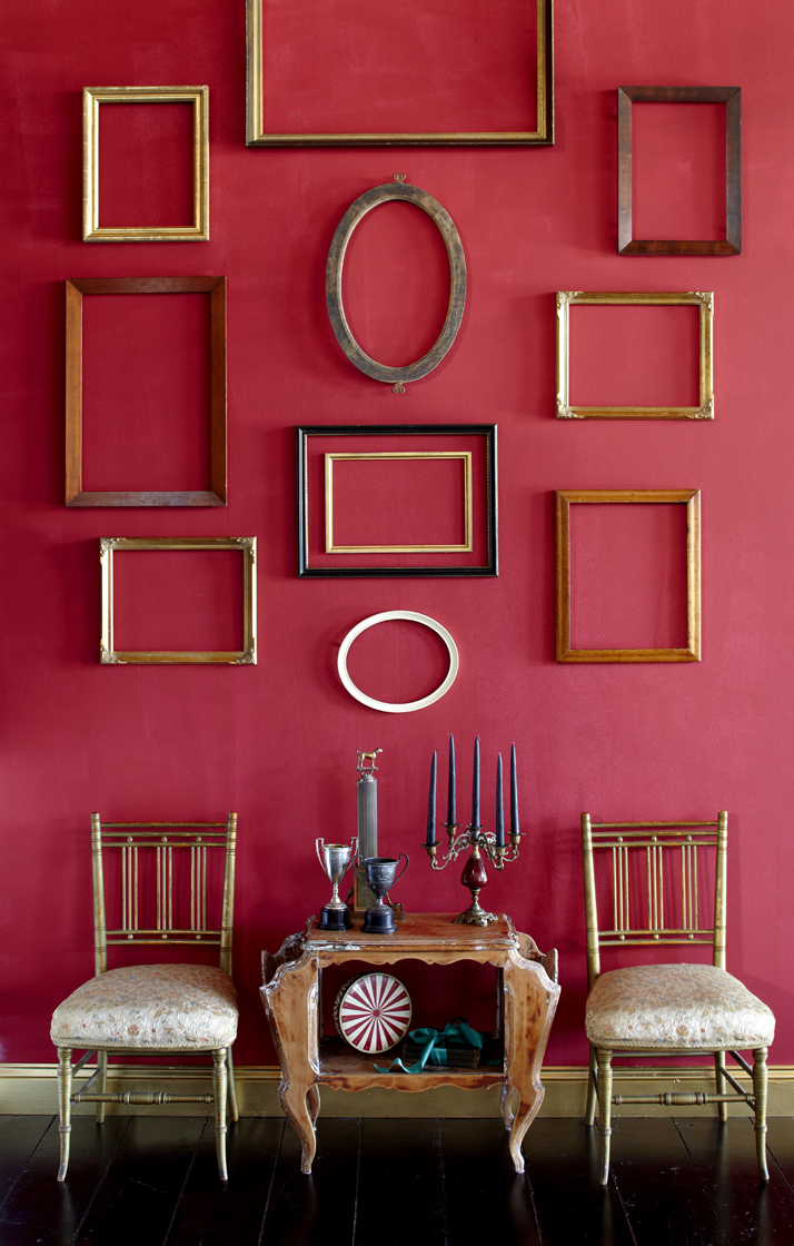 Empty frames on red wall with dining chairs.