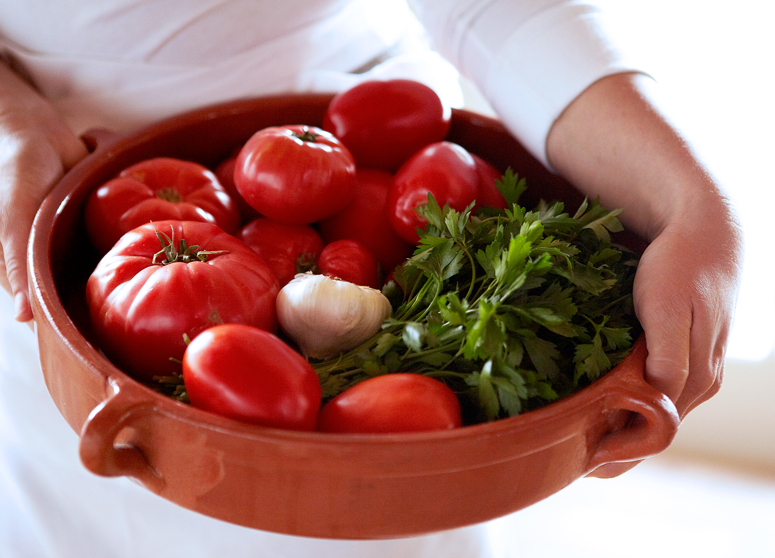 Woman Carrying Bowl of Tomatoes and Parsley